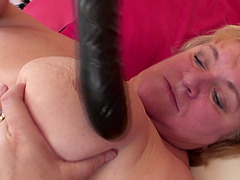 Evie enjoys drilling her gaping vagina with a black toy